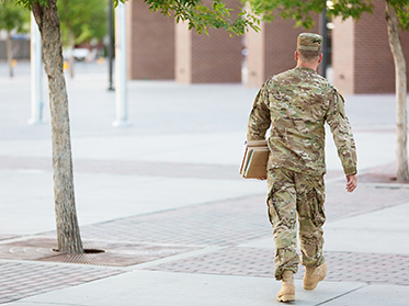 Student in Army fatigues carrying books across campus