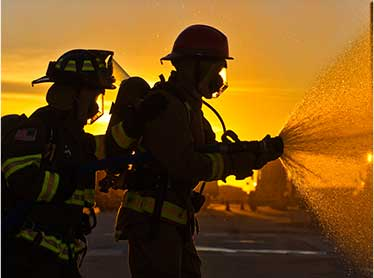 Two Fireman using a fire hose to take out a fire as the sunset goes down.